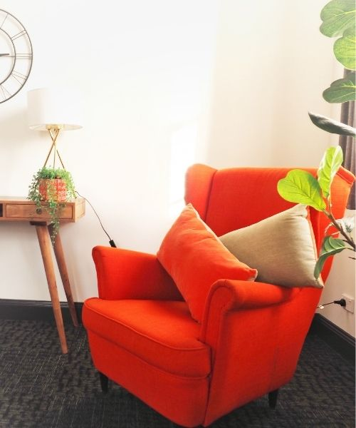 Orange couch in self contained apartment